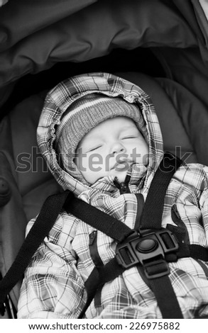 Adorable baby boy in winter clothes sleeping in stroller outdoor  ( black and white ) - stock photo