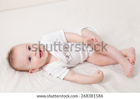 Adorable baby boy on his back playing and laughing - stock photo