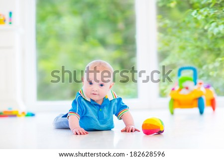 Adorable baby boy playing with a colorful ball and toy car in a sunny nursery with white furniture and white floor and a big garden view window - stock photo