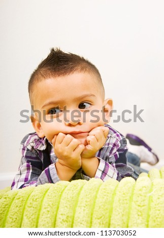 adorable baby boy portrait laying on a pillow with his nads under the chin - stock photo