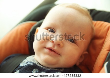 Adorable baby boy sitting in car seat - stock photo