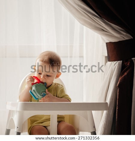 Adorable Baby Boy Sitting In High Chair And Playing With His Toy - stock photo