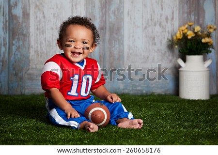 Adorable baby boy sitting in the grass, wearing a football uniform.   - stock photo