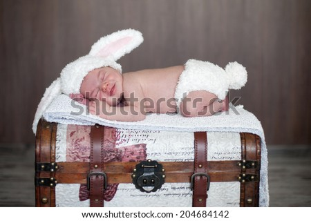 Adorable baby boy, sleeping on a trunk, dressed like bunny - stock photo