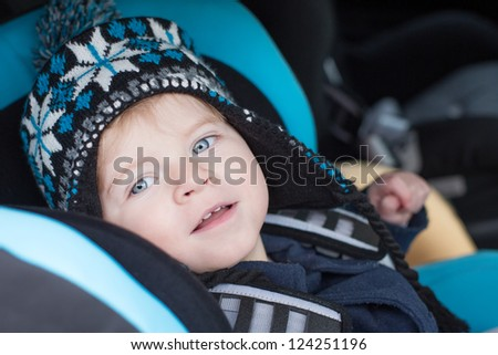 Adorable baby boy with blue eyes in safety car seat - stock photo