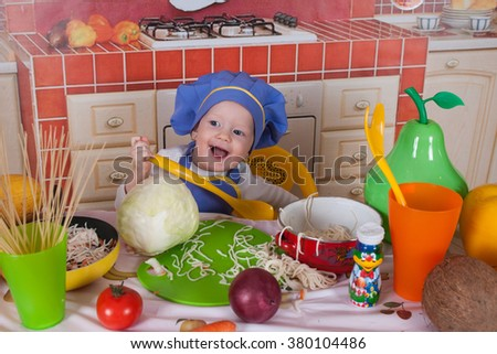 adorable baby cooking in kitchen. little cute child in costume of Cook. funny child makes a dinner. happy cute little baby in a cook cap laughs. Baby cook with vegetables in studio