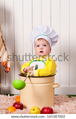adorable baby cooking in kitchen. little cute child in costume of Cook. Pretty beautiful boy covered in flour makes cakes.baby boy - stock photo