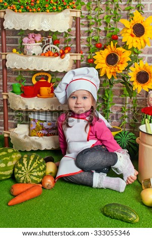 adorable baby cooking in kitchen. little cute child in costume of Cook.Pretty beautiful boy covered in flour makes cakes.Baby cook with vegetables in studio.happy cute little baby in a cook cap laughs - stock photo