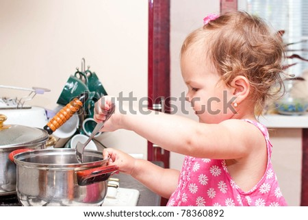 adorable baby cooking in the kitchen