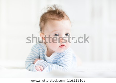 Adorable baby doing her tummy time in a white nursery