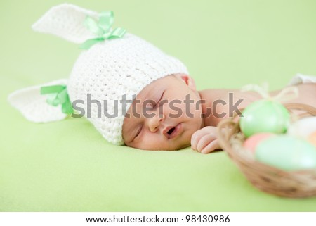 adorable baby dressed in Easter bunny cap with eggs - stock photo