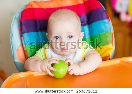 Adorable baby eating apple in high chair. Baby's first solid food - stock photo