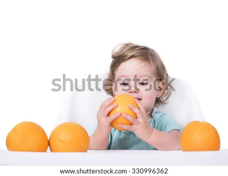 Adorable baby eating oranges, healthy food concept - stock photo