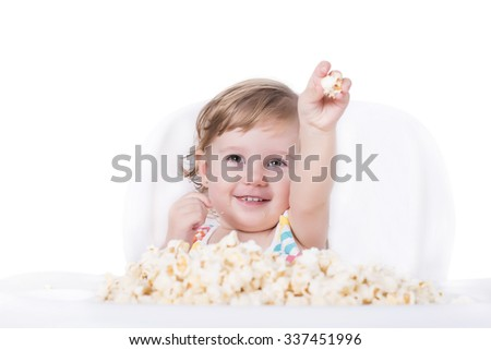 Adorable baby eating popcorn - stock photo