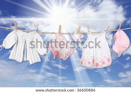 Adorable Baby Girl Clothes Hanging Outdoors - stock photo