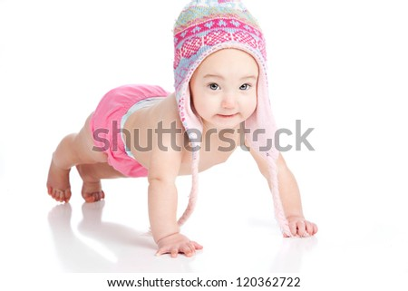 Adorable baby girl dressed in a winter hat and pink diaper cover doing a push-up.  Isolated on white. - stock photo