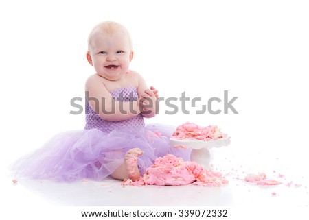 Adorable baby girl eating a birthday cake.  Isolated on white with room for your text.   - stock photo