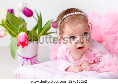Adorable baby girl in pink petty with tulips