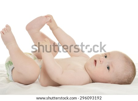 Adorable baby girl lying in pampers on blanket on a white background - stock photo