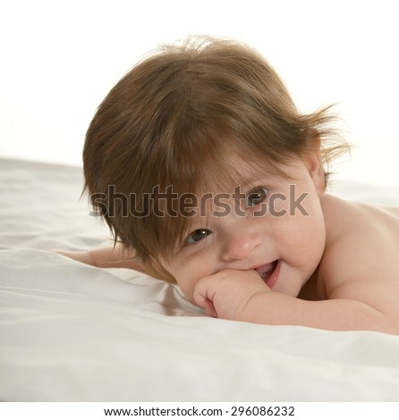 Adorable baby girl lying on a blanket on a white background - stock photo