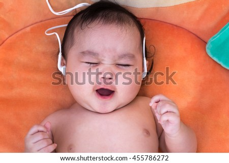Adorable baby girl music sounds good.newborn child relaxing and smile close up of face baby .2-6 months two-six months baby healthy concept. - stock photo