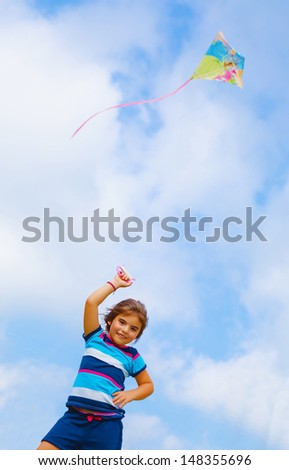 Adorable baby girl play with colorful kite outdoors, nice kid with toy on blue sky background, spending time in daycare, summer holidays concept - stock photo