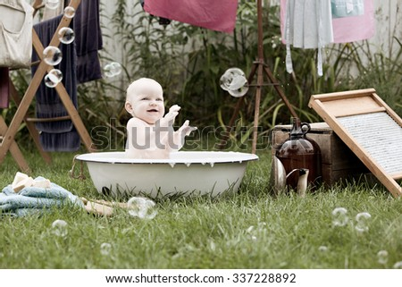Adorable baby girl playing in a vintage wash basin. Vintage clothes washing items scattered around and laundry hanging from a drying rack in the background.  Desaturated coloring for a vintage feel. - stock photo