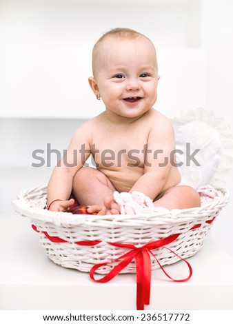 adorable baby girl playing in the basket - stock photo