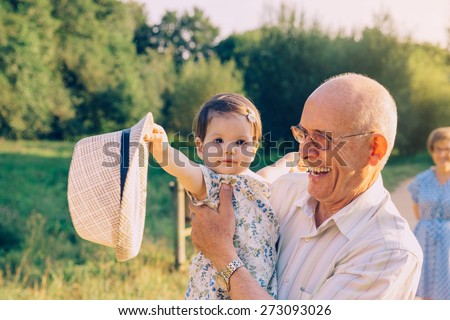 Adorable baby girl playing with the hat of senior man over a nature background. Two different generations concept. - stock photo