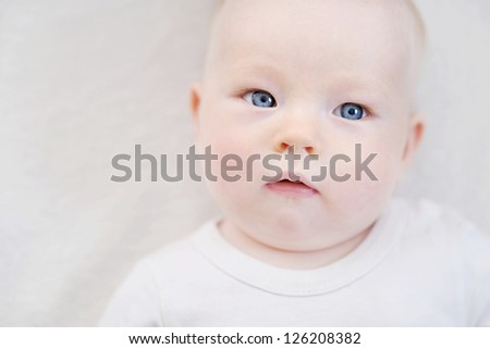 Adorable baby girl portrait on a white blanket