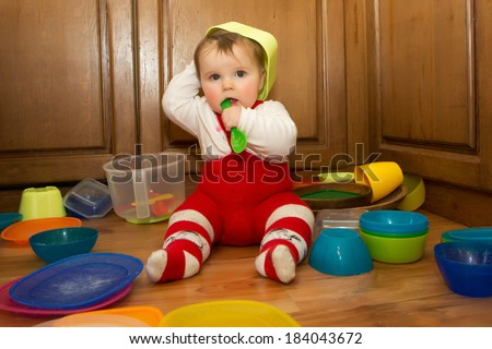 Adorable baby girl pulling pots and pans and other dishes out of a kitchen cupboard. - stock photo