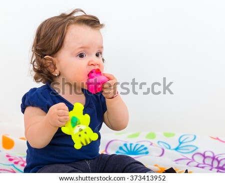 Adorable baby girl sitting on bed and nibbles the toy - stock photo