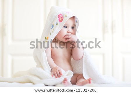 Adorable baby girl sitting under a hooded towel after bath