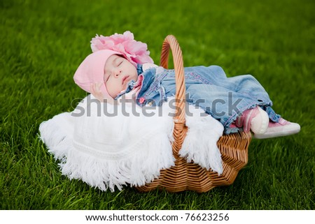 adorable baby girl sleeping in a basket in a park - stock photo