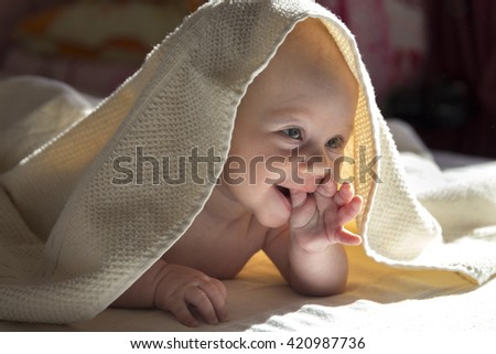 Adorable baby girl smiling covered in a shower towel - stock photo