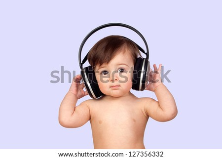 Adorable baby girl with big headphones isolated on a blue background - stock photo