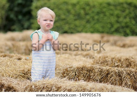 Adorable baby girl with blond hair standing in a middle of a hay labyrinth at halloween party in a farm - stock photo