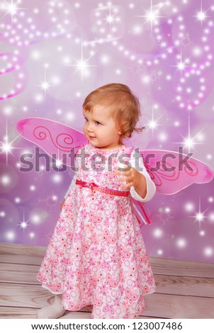 adorable baby girl with fairy wings on pink shining background - stock photo