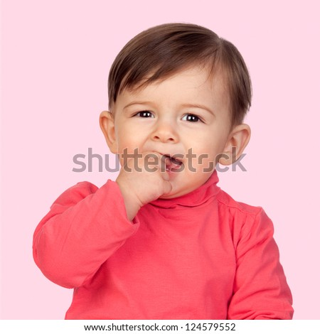 Adorable baby girl with her hand in mouth isolated on pink background - stock photo
