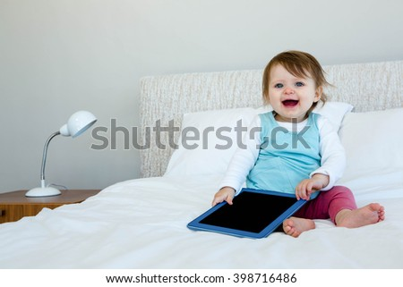 adorable Baby holding a tablet and sitting on a bed - stock photo