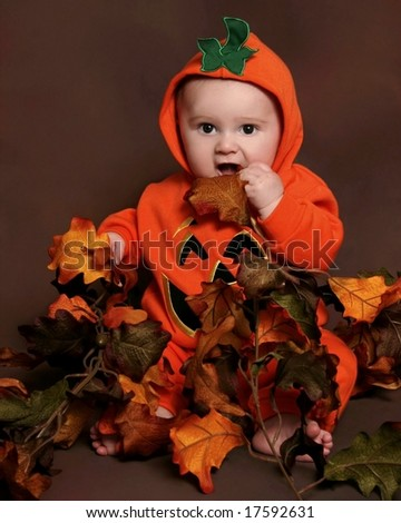 adorable baby in a pumpkin halloween costume - stock photo