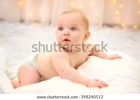 Adorable baby in diaper with pillows on the floor, close up - stock photo