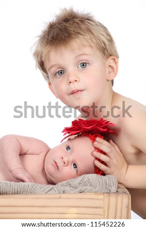 Adorable baby infant girl wearing red flower in hair, lying on soft brown blanket with her brother watching over her lovingly