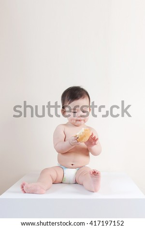adorable baby looking at the food in her hand - stock photo