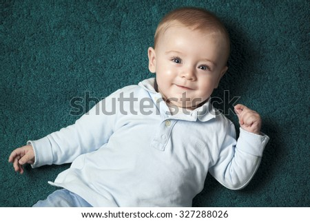 Adorable baby lying on a blue carpet and looking to the camera - stock photo
