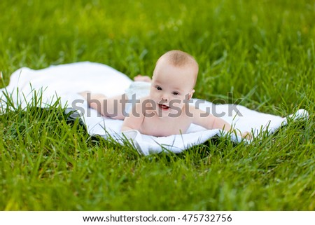 Adorable baby lying on green grass