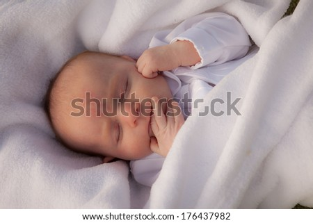 Adorable baby newborn boy sucking his fingers in a white baby blessing outfit - stock photo