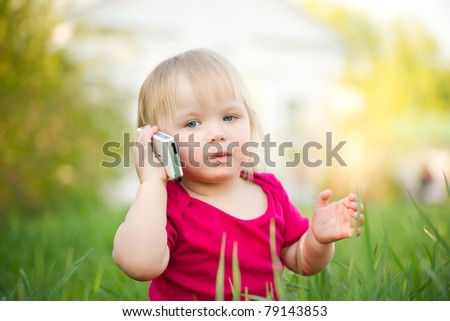 Adorable baby play with cell phone calling sitting in deep grass in park