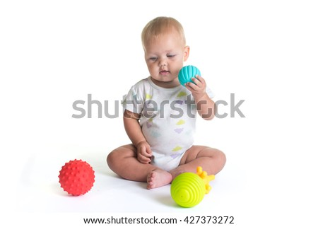 Adorable baby playing with a colorful beach ball, isolated on white