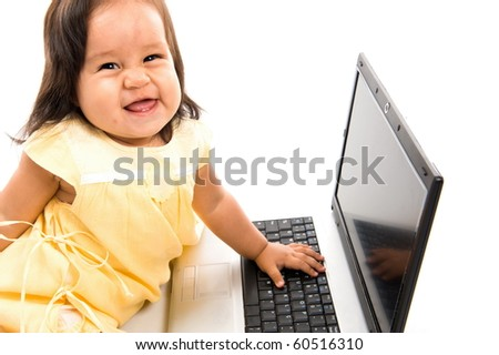 Adorable baby playing with the laptop . - stock photo
